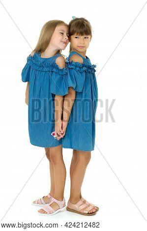 Smiling Girls Standing Back To Back. Adorable Girls Dressed In The Same Blue Dresses Posing Together