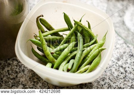 Fresh Whole Green Beans In A Bowl Over A Counter Top. Close Up.