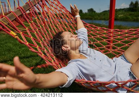 Happy Smiling Woman Relaxing On A Hammock On Holidays And Raising Arms On The Background Of A River