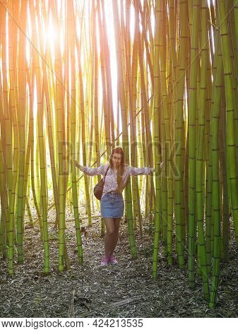 Smiling Girl Standing In Bamboo Grove Holding Tree Trunks On Warm Spring Day