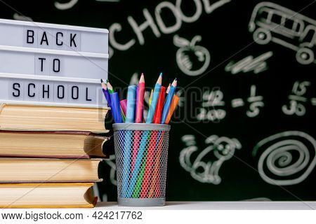 Back To School Background With Books, Pencils And Globe On White Table On A Green Blackboard Backgro