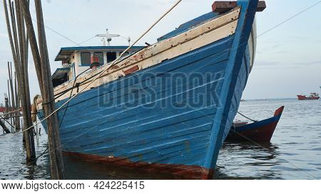 Fishing Boats Are Leaning On The Fishing Coast Of Dumai Town, A Blue Fishing Boat