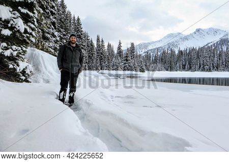 A Handsome Man Posing For A Photo Dressed In A Winter Coat And Toque, With A Forest And Lake In Back