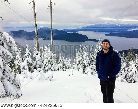 A Handsome Man Posing For A Photo Dressed In A Winter Coat And Toque, With The Forest And Ocean In T