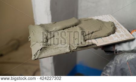 The Worker Holds A Ceramic Tile In His Hand. The Process Of Laying Ceramic Tiles In The Bathroom.