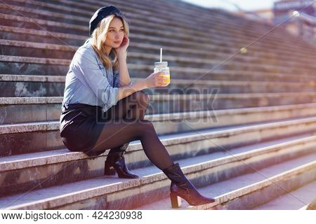Blonde Woman With Beret, Drinking A Natural Orange Juice In A Crystal Glass, Sitting On Some Steps.
