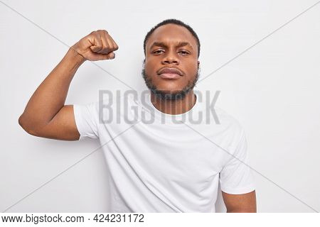 Serious Self Confident Black Man With Beard Raises Arm Shows Muscles Being Assured Feels Strong And