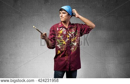 Young Emotional Artist Gesturing With Paintbrush. Caucasian Painter In Dirty Shirt And Bandana Stand