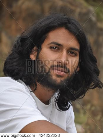 Close Up Shot Of A Handsome Bearded And Long Haired Young Men Sitting Outdoor And Looking At Camera,