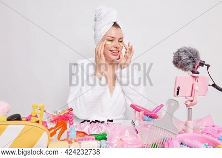 Skin Care And Beauty Concept. Glad Young European Woman Applies Cucumber Slices Under Eyes Smiles Gl