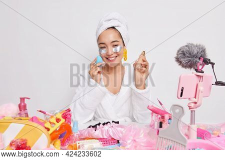Happy Woman Beauty Blogger In White Bathrobe Applies Foundation On Face Silver Patches Under Eyes Lo