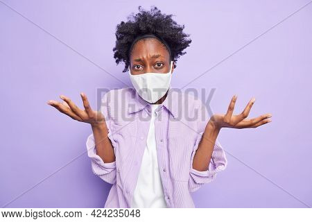 Flu Epidemic And Quarantine Time. Clueless Hesitant Dark Skinned Woman Wears Protective Face Mask Sp