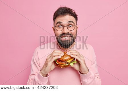Handsome Positive Guy Has Binge Eating Unhealthy Nutrition Holds Appetizing Hamburger Looks Gladfull