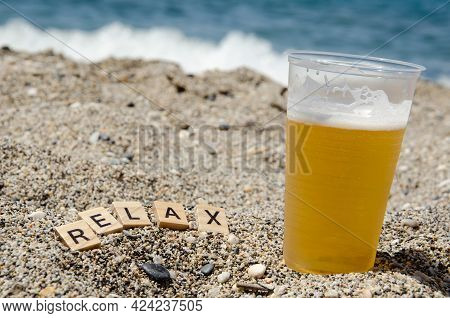 Lettering Relax Next To Glass Of Beer On Beach Against Background Of Blurred Turquoise Sea. Inscript