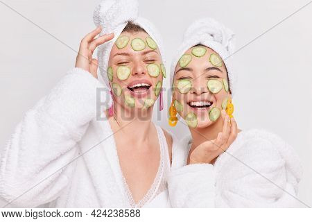 Cheerful Happy Young Women Enjoy Rejuvenation Treatments Apply Cucumber Slices On Face For Skin Care