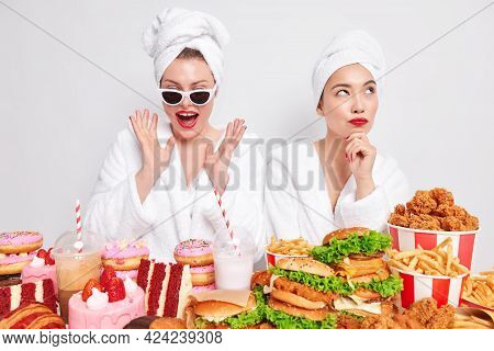 Indoor Shot Of Two Women Have Cheat Day Spend Free Time At Home Stand Near Delicious Snacks Wear Bat
