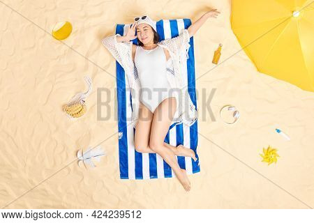 Vacation Time And Recreation. Relaxed Asian Woman Dressed In White Swimsuit Sunhat And Sunglasses Li
