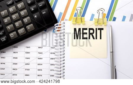Merit Text, Written On A Sticker With Calculator,pen On Chart Background.