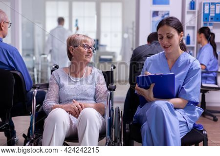 Assistant Taking Notes On Clipboard About Patient Madical Problems Waiting For Specialist Doctor Sit