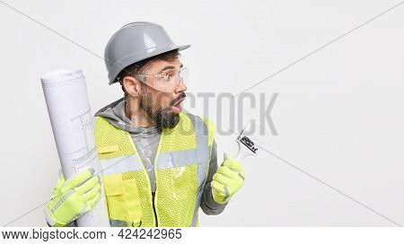 Indoor Shot Of Frightened Bearded Man Industrial Worker Poses With Blueprint And Painting Brush Wear
