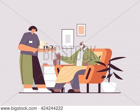 Female Nurse Or Volunteer Bringing Pills To Elderly Man Patient Home Care Services Healthcare And So
