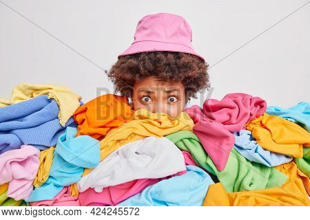 Worried Puzzled Woman Cluttered With Unfolded Mixed Up Clothes Raises Head Drom Heap Of Unfolded Mul
