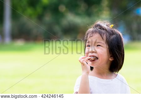 Asian Child Eating Chocolate. Cute Girl Biting Delicious Wafers. On Green Laws Nature Background. Su