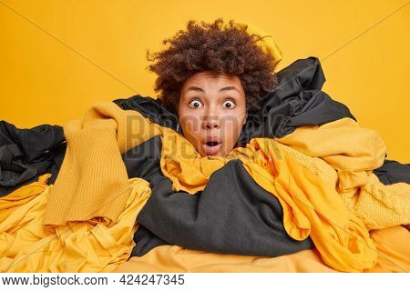 Shocked Curly Haired Woman Stunned By Big Sales In Second Hand Grabs Clothes Sticks Out Head Through