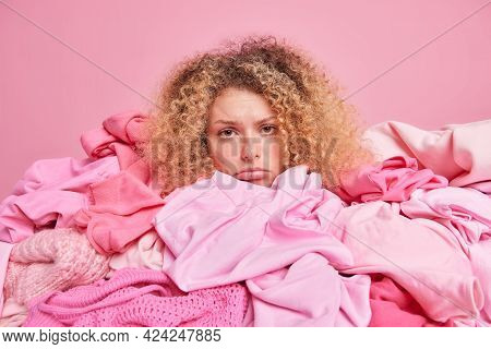 Discontent Curly Haired Woman Looks Sadly At Camera Has Helpless Expression Grabs Clothes In Retail