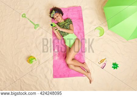 Summer Rest Concept. Smiling Relaxed Young Afro American Woman Uses Smartphone For Chatting Online W
