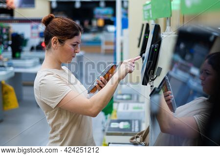 A Frustrated Woman Uses A Self-checkout Counter. The Girl Does Not Understand How To Independently B
