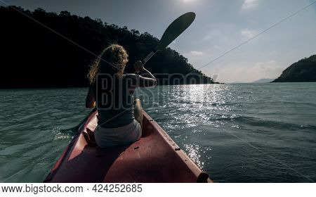 Silhouette Of Woman Tourist Raising Hands While Sailing In Canoe Along Sea Bay Water To Distant Hill