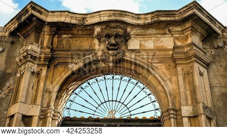 Catania, Piazza San Placido. An Unusual Smiling Face In The Upper Section Of A Gate.