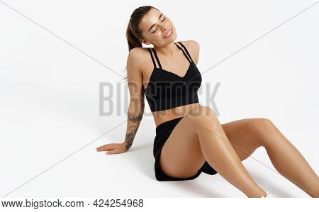 Female Athlete In Sports Clothing, Resting On Floor After Workout Jogging, Isolated On White Backgro