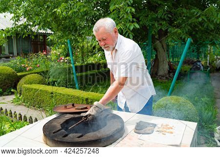 An Elderly Man With A Beard Opens The Lid Of A Tandoor In The Garden.