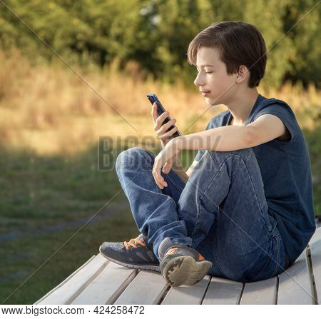 Teenager with Smartphone in Hand. Boy look in cell phone on summer background