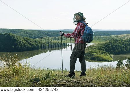 Man Hiker With Nets From Mosquitoes In Hiking Trip Near Lake Outdoors.