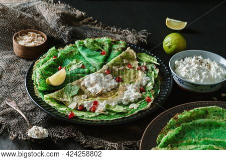 Green Vegan Crepes With Spinach Or Pancakes With Cottage Cheese, Pomegranate, Nuts And Spinach Leave