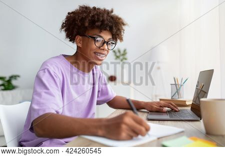 Home Schooling Concept. Smart Black Teen Guy Using Laptop At Table, Writing In Notebook During Onlin