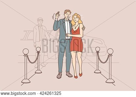 Famous Couple Waving To Camera Concept. Young Smiling Couple Stars In Elegant Clothing Standing In H