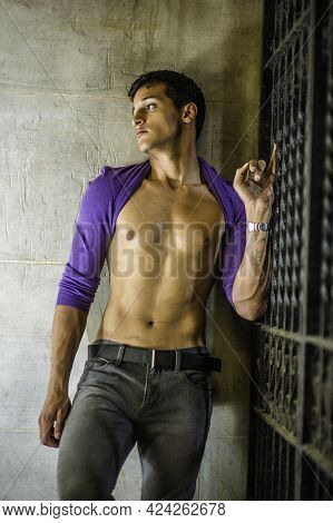 Standing On The Corner Between A Wall And A Metal Gate, A Sexy Young Guy Is  Rolling His Purple Swea
