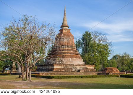 Ancient Buddhist Stupa In The Historical Park Of Sukhothai City On A Sunny Day. Thailand