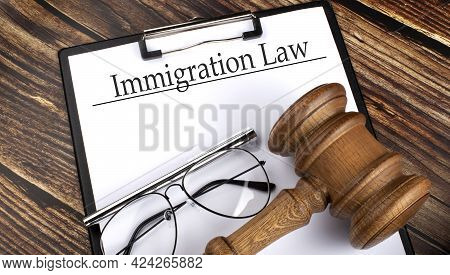 Immigration Law Text On The Paper Sheet With Gavel And Glasses On Wooden Background