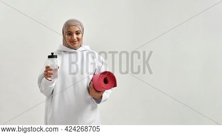 Smiling Young Arabic Woman In Hijab Holding Sport Mat And Bottle While Posing On Light Background Wi