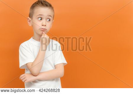 Portrait Of Funny Thoughtful Preschool Boy Keeps Hand Under Chin, Looks Away Trying To Remember Some
