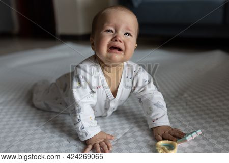 Authentic Lifestyle Photo Of Infant Baby Girl Seven Months Old Which Lying On Floor At Home And Cryi