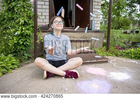 A Teenage Girl In Glasses With Multi-colored Hair Sits On The Porch Of The House And Draws On The Pa