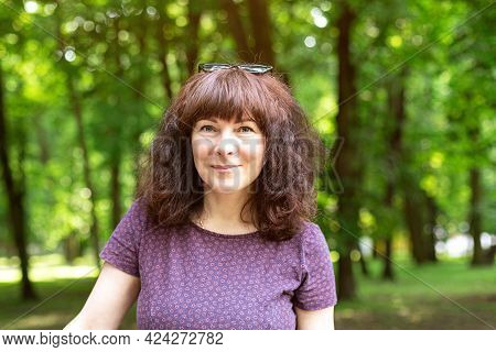 Nice Woman Of Forty Five Years Old With Brown Hair Looking At The Camera. Portrait Of Positive Confi