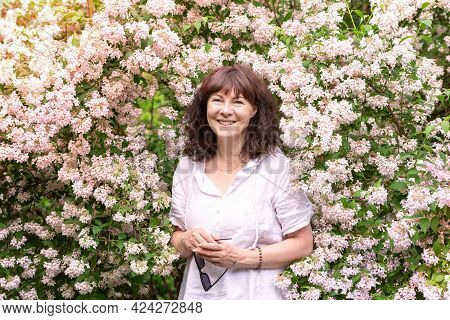 Portrait Nice Woman Of Forty Five Years Old With Brown Hair.stands Near Large Flowering Bush, Smilin