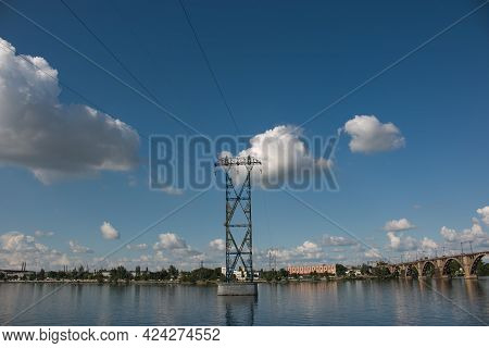 High-voltage Pylons Of Power Lines On The River. Metal Pylons Of High-voltage Power Line On Concrete